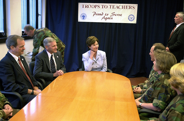Mrs. Bush and to her immediate right, Dr. John Gantz, Director of Troops to Teachers program, and retired Air Force Colonel Joseph Gaskin, a teacher from Raleigh, NC, discuss the Troops to Teachers program with interested Aviano Air Base members. On her first European visit, the First Lady of the United States visited Aviano Air Base, Italy Friday to promote the Troops to Teachers program. Mrs. Laura Bush spoke to more than 500 people in Hangar One about the rewards of teaching America's children and the need for qualified teachers nationwide. Currently 4,000 former military members have become teachers through the Troops to Teachers Program