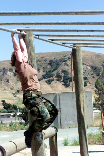 During Marine Week of the Career Orientation and Training of Midshipmen (CORTRAMID) West 2001 at Marine Corps Base (MCB) Camp Pendleton, California, midshipman Brittany Caranto swings her legs forward to mount the monkey bars on the obstacle course
