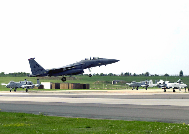 An F-15E Strike Eagle from the 494th Fighter Squadron, 48th Fighter Wing, Royal Air Force Lakenheath, United Kingdom, approaches the runway at Royal Air Force Lakenheath for landing while A-10 Thunderbolts from 81st Fighter Squadron, Spangdahlem Air Base, Germany, await take off in the Aircraft hold area