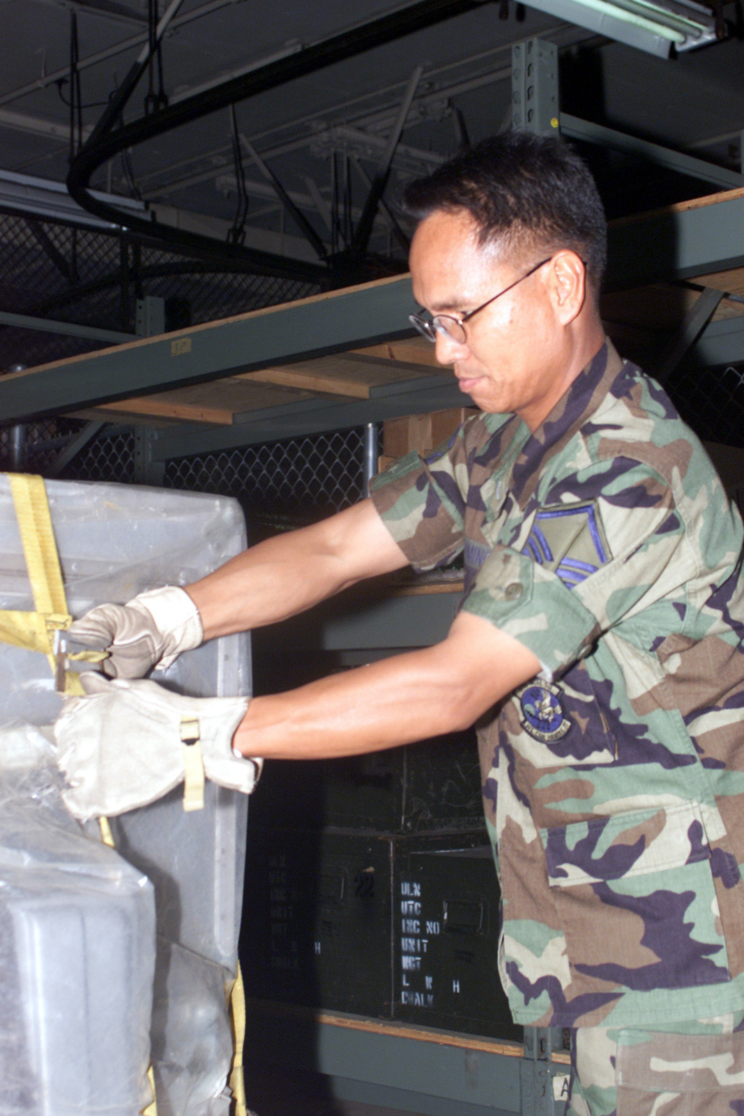 MASTER Sergeant Jesse Domingo, USAF, Assistant Corporate Information Manager from the 55th Communications Squadron, releases the top netting from the flight pallet during training for an upcoming ORE (Operational Readiness Exercise) exercise held at Offutt AFB