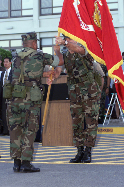 Marine Corps Base SGTMAJ, Sergeant Major (SGTMAJ) Pinon, hands the Marine Corps Base organizational colors to Lieutenant General (LTGEN) Earl B. Hailston, outgoing III MEF Commanding General during the III MEF change of command ceremony. After two years as Commanding General of III Marine Expeditionary Force/Marine Corps Bases Japan, LTGEN Earl B. Hailston, relenquished command to LTGEN Wallace C. Gregson during a sunset ceremony aboard Camp Courtney, Okinawa, Japan, on 010731
