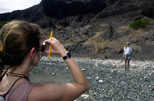 """Katie Comer (foreground) a Geologist with the San Diego Zoo uses a range finder to read the slope of the beach, as Tandora Grants, acts as a reference point, while conducting wildlife preservation research at Naval Station Guantanamo Bay, Cuba. From the US Navy (USN) """"ALL HANDS"""" Magazine, August 2001 Issue"""