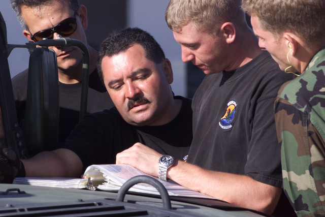 Technical Sergeant Eddy Santana, USAF, (left center) and STAFF Sergeant Timothy Dunlap, USAF, (right center), 615th Air Mobility Squadron, Travis Air Force Base, California, check the regulations for transport of a chalk of High-Mobility Multipurpose Wheeled Vehicle (HMMWV). The HMMWVs will be moved out of Marine Corps Air Station Miramar, San Diego, California, aboard a C-141 Starlifter from March Air Reserve Base, during this years PATRIOT HOOK Exercise. The PATRIOT HOOK Exercise 2001, a joint force exercise involving four separate airfields in Southern California - March Air Reserve Base, Marine Corps Air Station Miramar, Los Alamitos Army Air , and San Clemente Naval Landing...