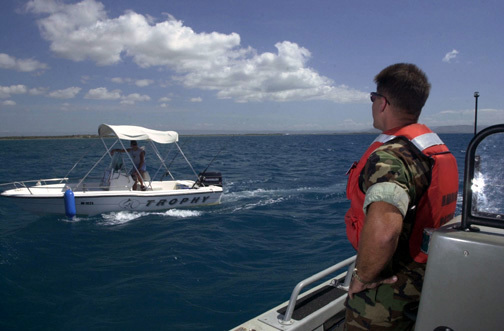 """US Navy (USN) Electronics Technician First Class (ET1) Surface Warfare (SW) Eric Fernelius, assigned to Harbor Patrol Unit Two (HP-2), hails a fisherman from his Rigid Hull Inflatable Boat (RHIB), while conduction Game Warden operations in the waters near Naval Station Guantanamo Bay, Cuba. From the US Navy (USN) """"ALL HANDS"""" Magazine, August 2001 Issue"""