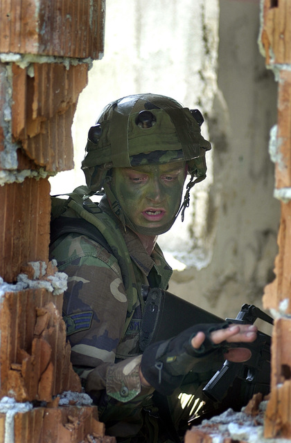 In full MILES (Multiple Integrated Laser Engagement System) and carrying a Colt 5.56 mm M16A2 rifle, SENIOR AIRMAN Craig Smelter, USAF, 31st Security Forces Squadron, Aviano Air Base, Italy, signals to his fire team members to take cover and stay down as he clears a building in a mock town. As part of Ground Combat Skills (GCS) training, the mission scenario is to move in and occupy a mock village, restore order and allow for peaceful elections. GCS is a weeklong training regiment consisting of three days of classroom work and two days in the field where trainees receive instruction on land navigation, combat patrolling and field craft skills