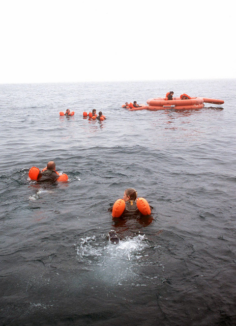 Aircrew members from the 128th Air Refueling Wing swim towards a twenty-man life raft during survival training exercise in Lake Michigan, Milwaukee, WI as parts of Exercise WHITETAIL 2001. The crewmembers are wearing their LPUs (Life Preserver Unit) with the floatation assembly fully inflated to aid their bouncy