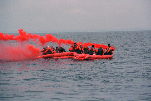Off the coast of Wisconsin on Lake Michigan, aircrew members from the 128th Air Refueling Wing, General Mitchell International Airport, Milwaukee, Wisconsin, onboard their LRU-15/F-2B 20 Man Life Rafts, light signal flares during survival training. The red smoke will help them stand out against the gray water when the rescue aircraft close in on them. The aircrews are part of Exercise WHITETAIL 2001