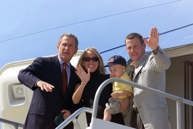 President George W. Bush and three-time Tour-De-France winner, Lance Armstrong (right) with his wife Kristin and son Luke, greet fans and visitors from the door of Air Force One upon their arrival at Robert Gray Army Airfield