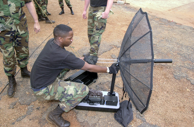SENIOR AIRMAN Larry Senegal, USAF, Command and Control Journeyman, 86th Contingency Response Group, Ramstein Air Base, Germany, assembles a TCS-Ultralite satellite terminal, a mobile communications unit, at the airfield in Accra, Ghana, in preparation to transport US forces and cargo involved in Operation FOCUS RELIEF. Operation FOCUS RELIEF, a United Nations peacekeeping operation in Sierra Leone, to equip and train seven battalions from West African countries to be able to conduct peace enforcement operations