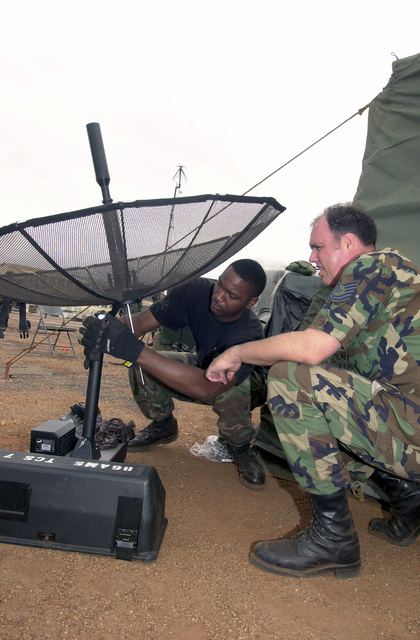 SENIOR AIRMAN Larry Senegal, USAF, (left), Command and Control Journeyman, and Technical Sergeant Darryl Moser, USAF, Communications SPECIALIST, both with the 86th Contingency Response Group, Ramstein Air Base, Germany, assemble TCS-Ultralite satellite terminal, a mobile communications unit, at the airfield in Accra, Ghana. In preparation to transport US forces and cargo involved in Operation FOCUS RELIEF. Operation FOCUS RELIEF, a United Nations peacekeeping operation in Sierra Leone, to equip and train seven battalions from West African countries to be able to conduct peace enforcement operations