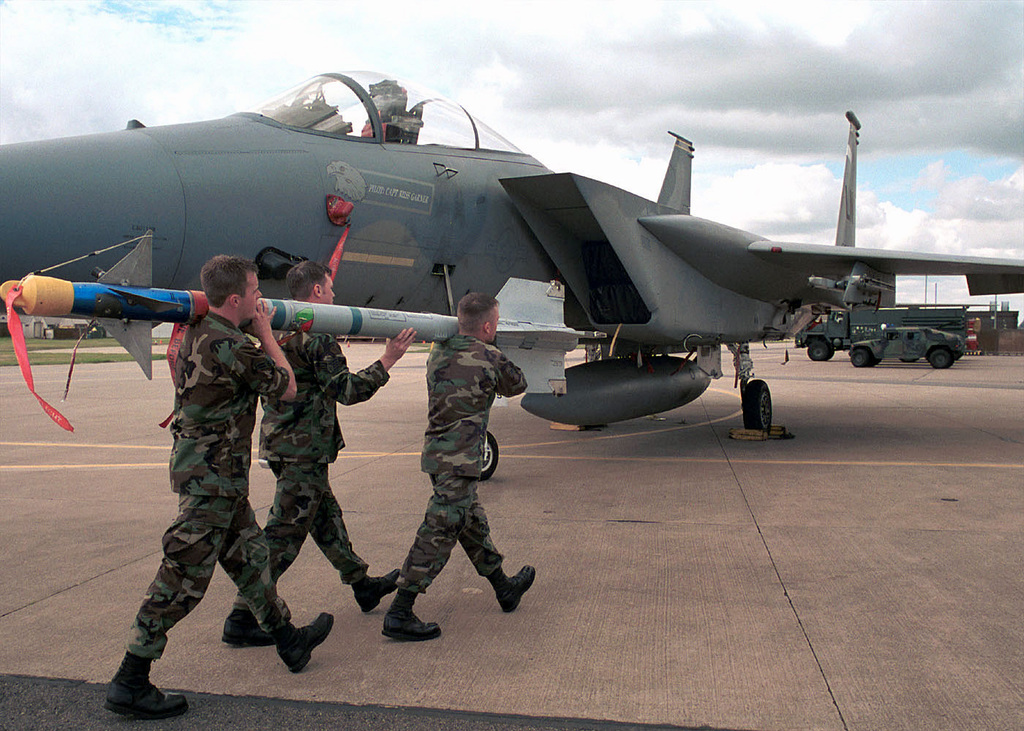 Carrying a Captive-9 training missile to a waiting F-15 Eagle are, left to right, STAFF Sergeant Shawn Mullins, AIRMAN First Class Christopher Hubler, and A1C Jeffery Bower all from the 493rd Fighter Squadron, 48th Tactical Fighter Wing