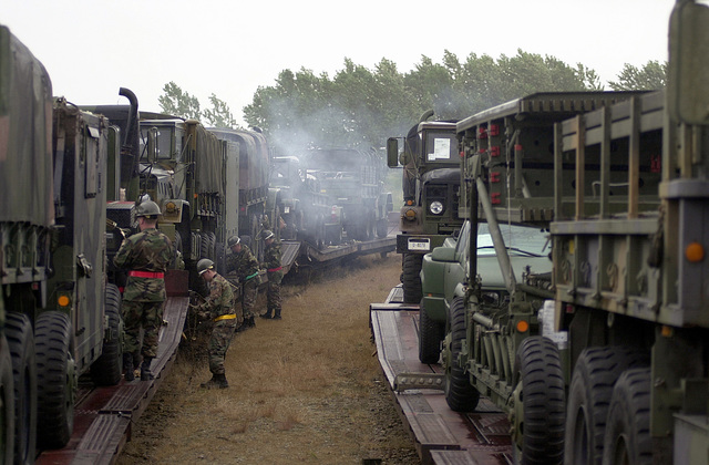 Personnel from the 603rd Air Control Squadron, Aviano Air Base, Italy, off-load M939A2, and M923, 5 Ton Trucks, from vehicle rail cars at a rail yard in Herning, Denmark