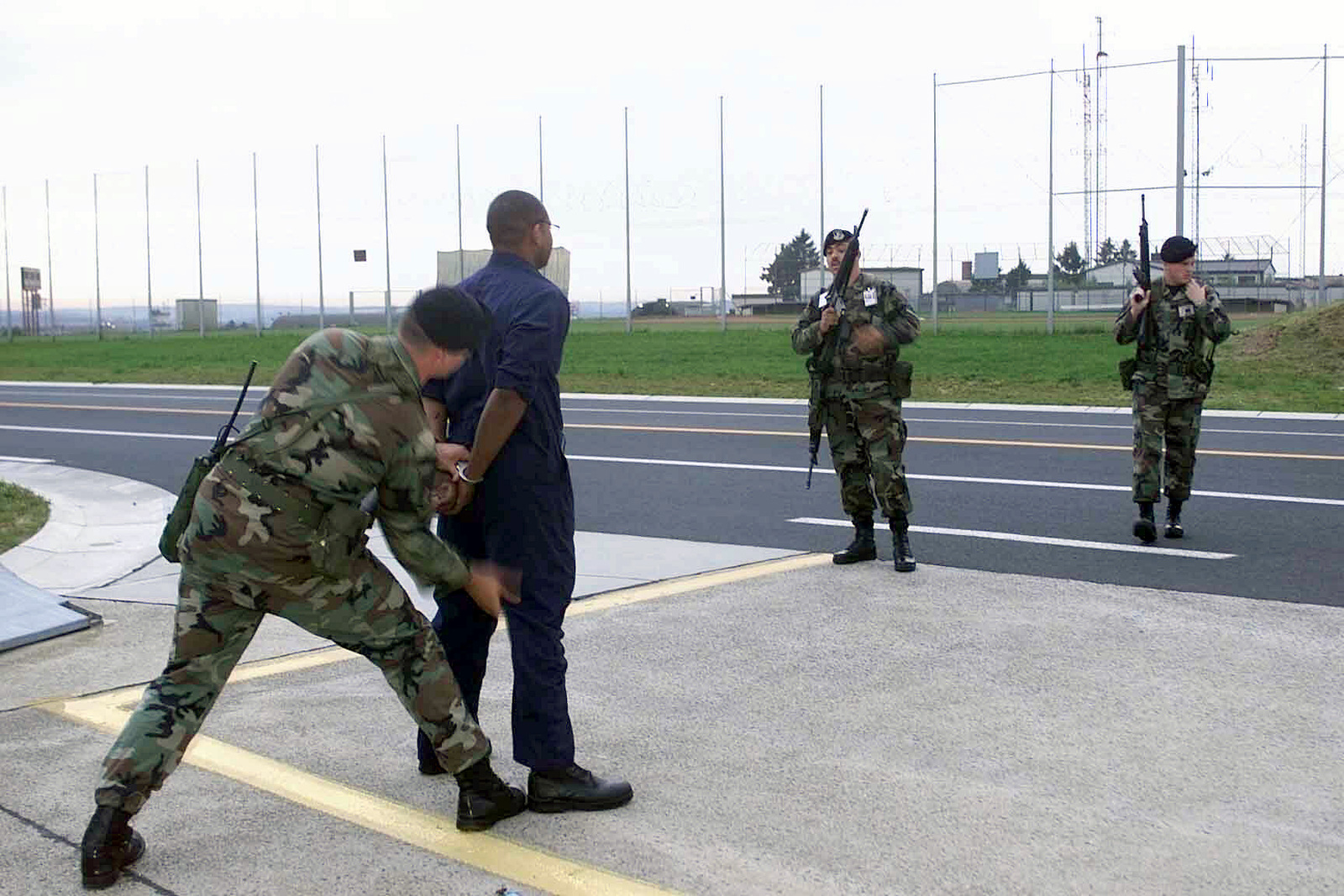 AIRMAN First Class Jason Jacobs searches an apprehended trespasser, STAFF Sergeant James Blakely a 23rd Fighter Squadron Crew CHIEF, and volunteer bad guy, while, SENIOR AIRMAN Julio Figueroa, center, and SSGT Kenneth Genter guards the scene during a security test at Spangdahlem Air Base, Germany