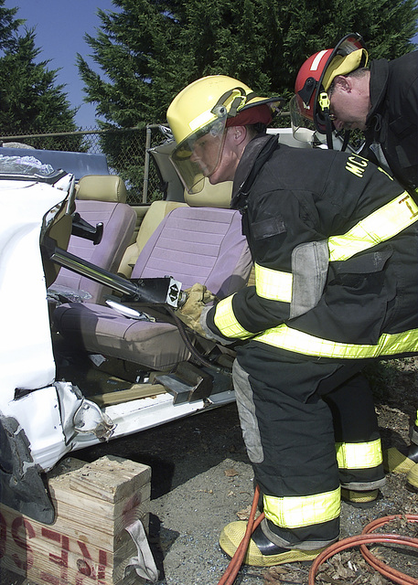 "US Air Force (USAF) AIRMAN (AMN) Michael Zedro, Fire Fighter, 305th Civil Engineering Squadron, begins a ""Dashboard Roll"" utilizing a 60-inch push ram during a ""Vehicle Extraction"" training exercise at McGuire AFB, New Jersey (NJ). The ram exerts force to roll the dashboard off a victim trapped in a car"
