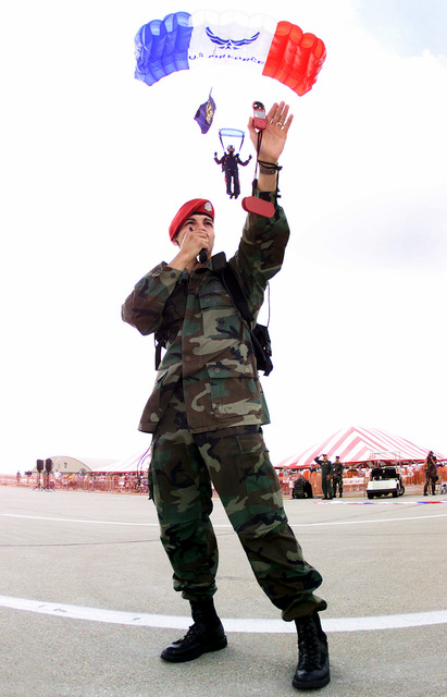 As Air Force Stars Jump Team member appears to drop onto his shoulder, STAFF Sergeant Ray Herrera, USAF, 22nd Special Tactics Squadron, McChord Air Force Base, Washington, transmits wind velocities from a Kestrel 300 wind meter to the incoming team during a HARP (High Altitude Release Point) landing at the 2001 Airshow at Offutt Air Force Base