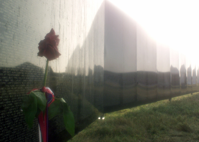 "The sun rises on names engraved on the replica of the original Vietnam War Memorial at the 2001 Airshow at Offutt Air Force Base. Many people visited ""The Wall That Heals"" during the Airshow and left mementos, such as this rose, in memoriam of those who died during the Vietnam War. The original memorial is located in Washington D.C"
