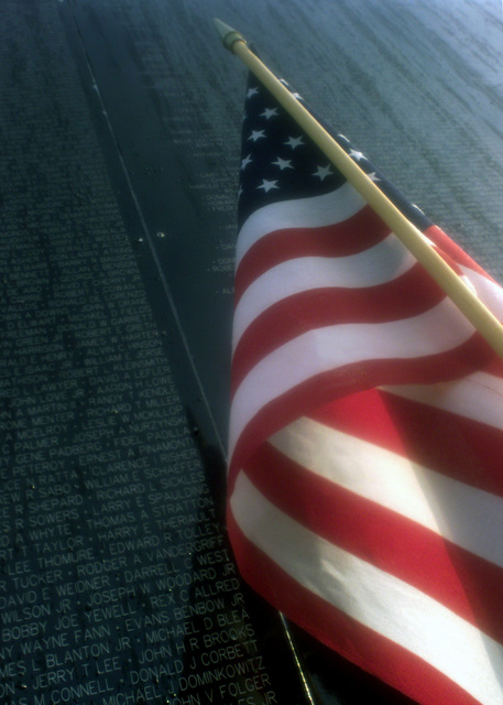 "The sun rises on names engraved on the replica of the original Vietnam War Memorial at the 2001 Airshow at Offutt Air Force Base. Many people visited ""The Wall That Heals"" during the Airshow and left mementos, such as this American flag, in memoriam of those who died during the Vietnam War. The original memorial is located in Washington D.C"