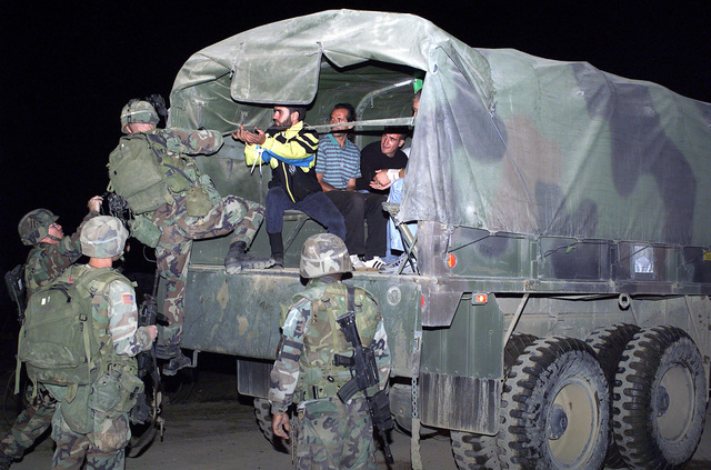 A group of ethnic Albanian rebels from the National Liberation Army (NLA) are loaded on to trucks and for transport to a detention center in Zegra, Kosovo, during Operation JOINT GUARDIAN II