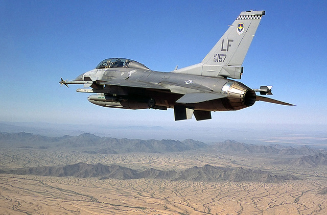 An F-16D Fighting Falcon from the 61st Fighter Squadron, Luke AFB, Arizona, flies a local training mission. The F-16 is carrying two AIM-9 training missiles, a SUU-20 Practice Bomb Dispenser, and a 370 gal tank