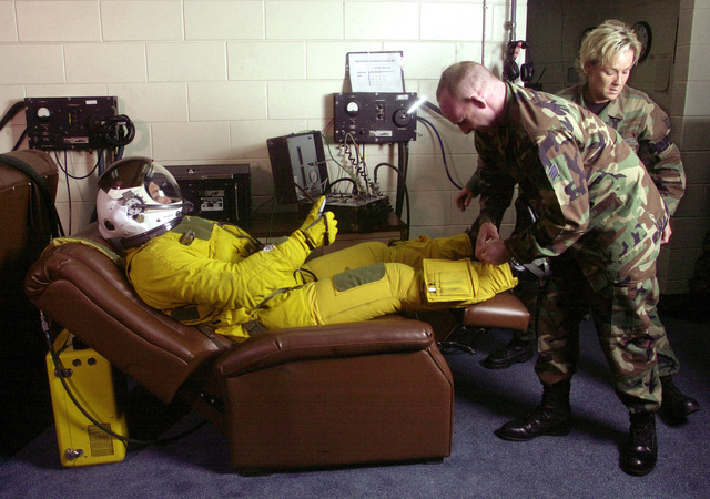 SENIOR AIRMAN Hank Webb, USAF, (center) and STAFF Sergeant Erin Manley,, USAF, both Aerospace Physiological Support specialists from the 5th Reconnaissance Squadron (Black Cats), Osan Air Base, Korea, adjust the straps on the pressure suit of U-2R Dragon Lady pilot Captain Michael Wheeler before a mission. Because of the altitudes that the aircraft can reach, a U-2R pilot has to wear a full-pressure suit similar to those worn by astronauts