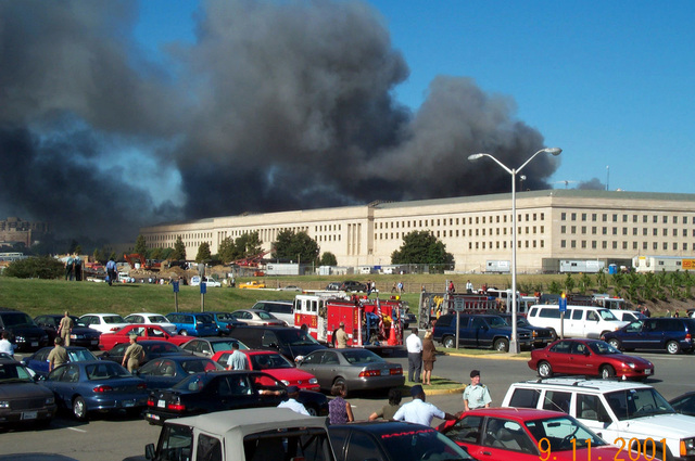 A view from the parking lot on the Metro Concourse side of the Pentagon as smoke and flames rise from the impact point on the Helicopter Landing Pad side of the building after it was struck by hijacked civilian airliner