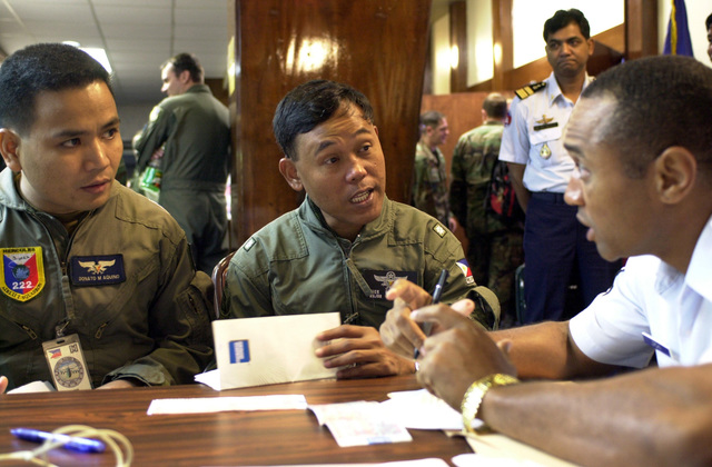 Captain Donato M. Aquino, (left), 220 Airlift Wing, Mactan Air Base, Philippine Air Force, and Major Nicolas C. Parilla, Headquarters Philippine Air Force (HPAF), receive assistance from MASTER Sergeant Horace Jordan Jr., USAF, Headquarters Pacific Air Force (HQ PACAF), concerning finances during their travel to Andersen Air Force Base, Guam. PACIFIC AIRLIFT RALLY (PAR) 2001 is a PACAF-sponsored Military Airlift symposium for countries in the pacific region. PAR, held every two years and hosted by a pacific nation, this year Guam is the host nation with the symposium staging out of Andersen AFB. The symposium includes informational seminars with area of expertise briefings, a Command Post...