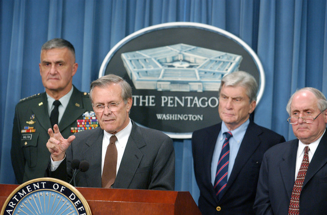 Defense Secretary Donald Rumsfeld addresses reporters in the Pentagon Press Room, soon after the attack on the Pentagon, accompanied on his right by Joint Chiefs of STAFF, U.S. Army GEN. Henry Shelton and on his left by U.S. Senator John Warner of Virginia and Carl Levin of Michigan, far left. (DoD photo by PETTY Officer 2nd Class Robert Houlihan) (Released)