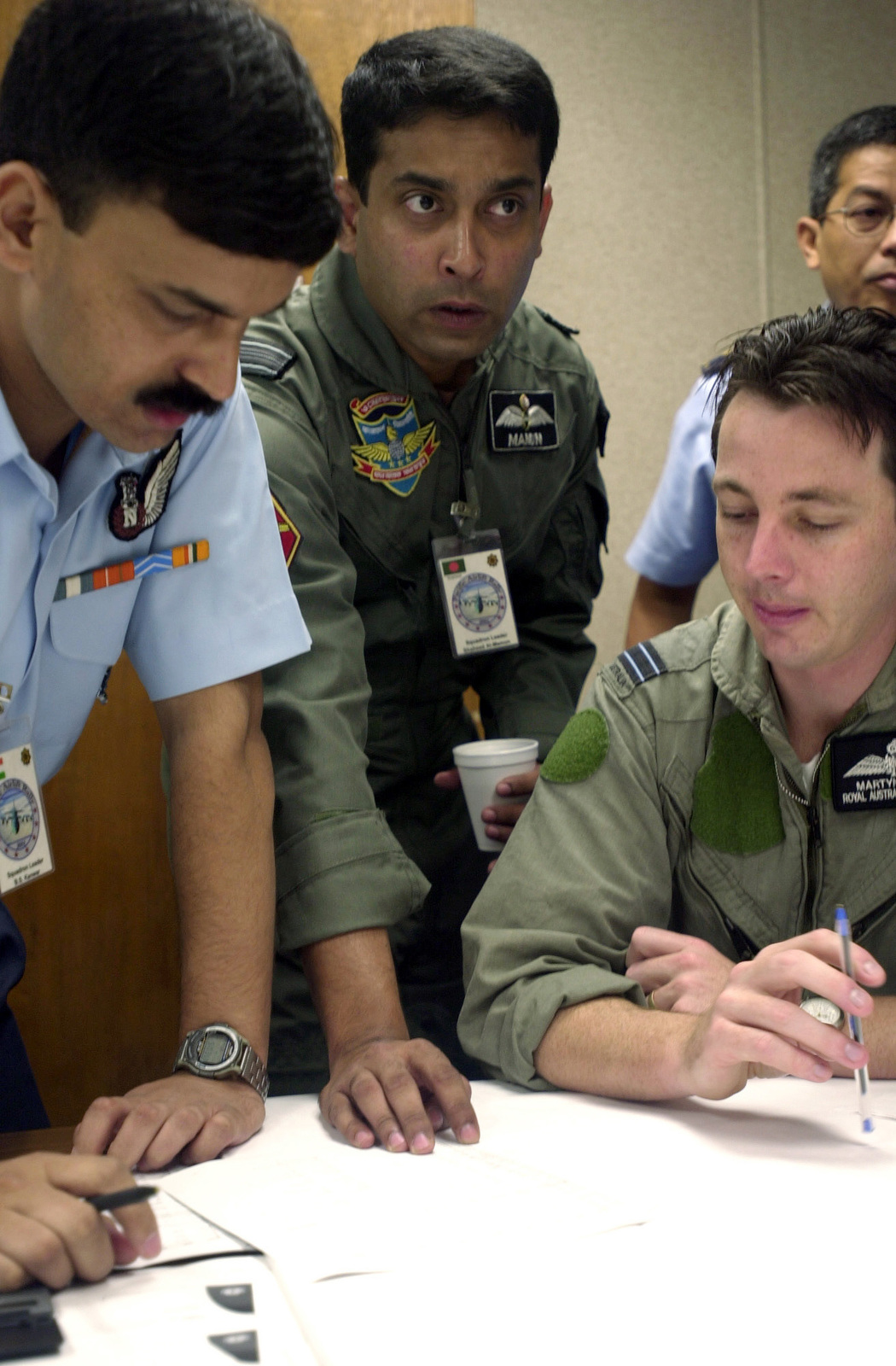 Squadron Leaders, B.S. Kanwar, (left), Indian Air Force, and Shaheed Al-mamun, Bangladesh Air Force along with Flight Lieutenant Martyn Silver, (right), Royal Australian Air Force exchanges ideas about flightline activities in preparation for PACIFIC AIRLIFT RALLY 2001 on Andersen AFB, Guam. PACIFIC AIRLIFT RALLY (PAR) is a PACAF-sponsored Military Airlift symposium for countries in the pacific region. PAR, held every two years and hosted by a pacific nation, this year Guam is the host nation with the symposium staging out of Andersen AFB. The symposium includes informational seminars with area of expertise briefings, a Command Post Exercise (CPX) which addresses military airlift support...