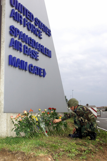 At the front gate of Spangdahlem Air Base, Germany, an unidentified US Air Force member arranges the flowers left by Americans and local German nationals in memory of the victims of the terrorist attacks on the World Trade Centers Twin Towers in New York and at the Pentagon. When hijackers deliberately flew civilian airliners into the buildings, on the morning of 11 September 2001