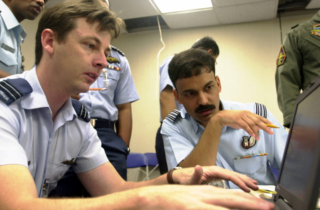 Flight Lieutenant Martyn Silver (left) of the Royal Australian Air Force and Squadron Leaders, B.S. Kanwar, Indian Air Force, review data about operations procedures in preparation of PACIFIC AIRLIFT RALLY 2001 on Andersen Air Forced Base, Guam. PACIFIC AIRLIFT RALLY (PAR) is a PACAF-sponsored military airlift symposium for countries in the pacific region. PAR is held every two years and is hosted by a pacific nation. This year Andersen AFB, Guam is the host nation. The symposium includes informational seminars with area of expertise briefings, a Command Post Exercise (CPX) which addresses military airlift support to a humanitarian airlift/disaster relief scenario, and a concurrent flying...