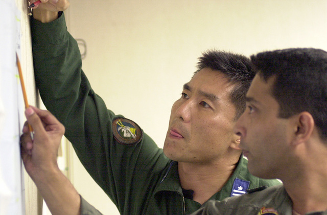 Major Tsuyoshi Ishida, (left), of Japan and Squadron Leader Shaheed Al-mamun, Bangladesh Air Force calculate drop zone targets in preparation for PACIFIC AIRLIFT RALLY 2001. PACIFIC AIRLIFT RALLY (PAR) is a PACAF-sponsored Military Airlift symposium for countries in the pacific region. PAR, held every two years and hosted by a pacific nation, this year Guam is the host nation with the symposium staging out of Andersen AFB. The symposium includes informational seminars with area of expertise briefings, a Command Post Exercise (CPX) which addresses military airlift support to a humanitarian airlift/disaster relief scenario, and a concurrent flying training program that builds upon the CPX ...