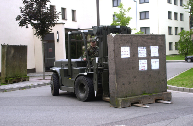 Members of the 86th Transportation Group use a Hyster forklift to put up barriers around the 86th Airlift Wing Headquarters Building in response to Condition Threatcon Delta on Ramstein Air Base, Germany. The base is now operating in a heighten state of alertness in response to terrorist attacks on the World Trade Centers Twin Towers in New York and at the Pentagon, when hijackers deliberately flew civilian airliners into the buildings, on the morning of 11 September 2001