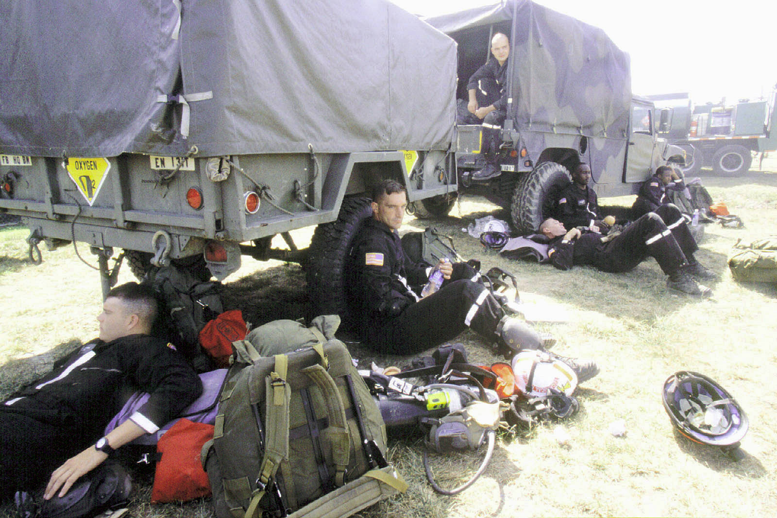 Military District of Washington (MDW) Engineer Company (Technical Rescue) engineers rest in e shade of a M1097 High-Mobility Multipurpose Wheeled Vehicle (HMMWV) and M105 trailer before going back inside e Pentagon to search for more bodies on September 12, 2001. The morning before, in an attempt to frighten e American people, five members of Al-Qaida, a terrorist group of fundamentalist Muslims, hijacked American Airlines Flight 77, en flew a circuitous route returning to Washington and impacting e Pentagon killing all 64 passengers onboard and 125 people on e ground. The impact destroyed or damaged four of e five rings in at section of e building. Firefighters fought...