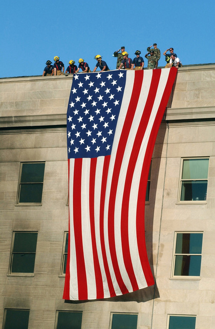Soldiers from the 3rd Infantry render honors as fire fighters and rescue workers unfurl a huge American flag over the side of the Pentagon as rescue and recovery efforts continued following the September 11, 2001 terrorist attack. The flag, a garrison flag, sent from the US Army Band at nearby Fort Myer, Virginia, is the largest authorized (20 x 38) flag for the military. Shortly after 8 AM on September 11, 2001 in an attempt to frighten the American people, five members of Al-Qaida, a group of fundamentalist Islamic Muslims, hijacked American Airlines Flight 77, a Boeing 757-200, from Dulles International Airport just outside Washington DC. About 9:30 AM they flew the aircraft and 64 ...