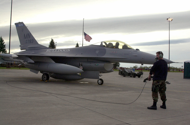 """Taking back the night, a 148th Fighter Wing Crewchief and Pilot conduct last minute operational checks of a Minnesota Air National Guard F-16 ADF (Air Defense Fighter) """"Fighting Falcon"""", prior to a night CAP (Combat Air Patrol) assigned by NORAD. The FAA called on the 148th Fighter Wing to enforce the ban on all commercial fight activity following the terrorist attacks on September 11, 2001 at the World Trade Center and the Pentagon. The flag rests at half-mast in the background in memory of those lost lives"""