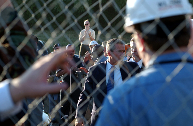 US President George W. Bush visits the Pentagon to survey damage and commend the joint rescue and recovery efforts currently underway the following the September 11, 2001, terrorist attack. The morning before, in an attempt to frighten the American people, five members of Al-Qaida, a terrorist group of fundamentalist Muslims, hijacked American Airlines Flight 77, then flew a circuitous route returning to Washington and impacting the Pentagon killing all 64 passengers onboard and 125 people on the ground. The impact destroyed or damaged four of the five rings in that section of the building