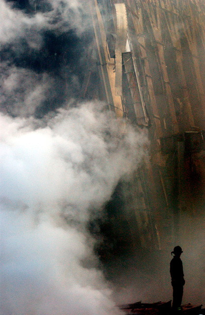 A solitary Firefighter stands watching as smoke rises from the rubble and debris of the World Trade Centers in New York City in the area known as Ground Zero, after the 9/11 terrorists attacks