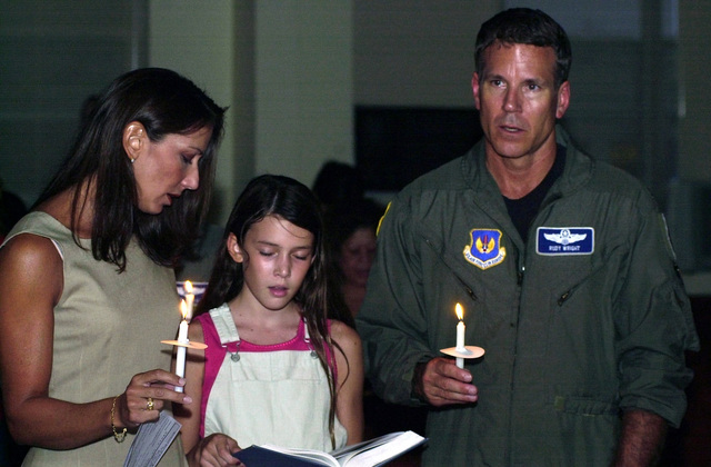 Colonel Rudy Wright, USAF, Commander 39th Wing and 39th Air and Space Expeditionary Wing, his wife, Samantha, and daughter, Jordan, sing America the Beautiful and offer prayers for the thousands of Americans lost during the terrorist attacks on the World Trade Centers Twin Towers and at the Pentagon. The candle light vigil was held at the base chapel at Incirlik Air Base, Turkey, in conjunction with National Prayer Day and Remembrance declared by President George W. Bush, 14 September 2001