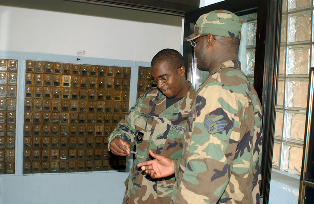 Due to increased security, SENIOR AIRMAN (SRA) Derek Brockington, 786th Communications Squadron, Ramstein Air Base, Germany, checks the identification card of a 86th Airlift Wing member before he enters the Southside Post Office. Security measures have increased at all military installations worldwide due to the terrorist attacks in the United States