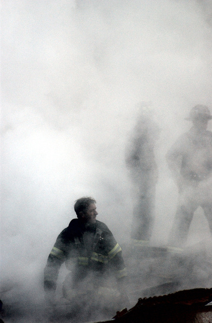 Firefighters brave the thick smoke as they search for survivors through the rubble and debris of the World Trade Centers in New York City in the area known as Ground Zero, after the 9/11 terrorists attacks