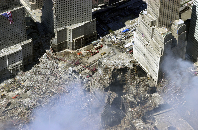 An aerial view, days after the terrorist attacks on American soil, the towers of the World Trade Center (WTC) sit as a pile of rubble in the streets of New York City. The rescue and recovery efforts continue with tons of debris slowly removed from the site. The view is toward the northwest, with an American flag draped on World Financial Center (WFC) tower two, and the Verizon Building on the right