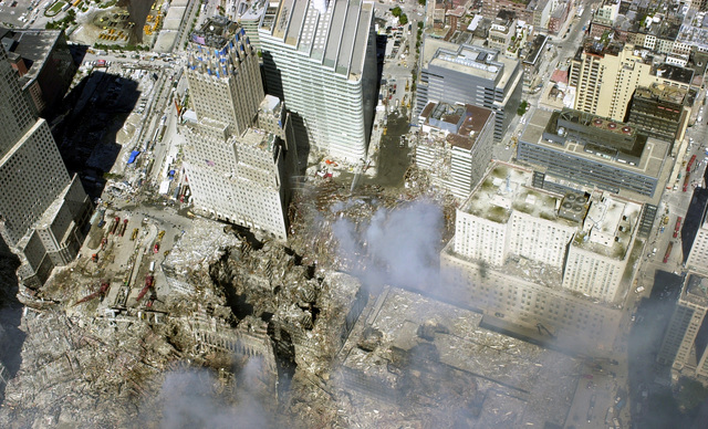 An aerial view, days after the terrorist attacks on American soil, the towers of the World Trade Center (WTC) sit as a pile of rubble in the streets of New York City. The rescue and recovery efforts continue with tons of debris slowly removed from the site. The view is toward the northeast, World Financial Center (WFC) tower three (American Express) (left), the Verizon Building (with 75 Park Place behind it) and the US Post Office (right)