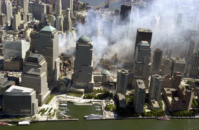 An aerial view, days after the terrorist attacks on American soil, the towers of the World Trade Center sit as a pile of rubble in the streets of New York City. The rescue and recovery efforts continue with tons of debris slowly removed from the site. The view is to the east, in the foreground the Hudson River and The North Cove Marina with the World Financial Center (WFC) towers behind it