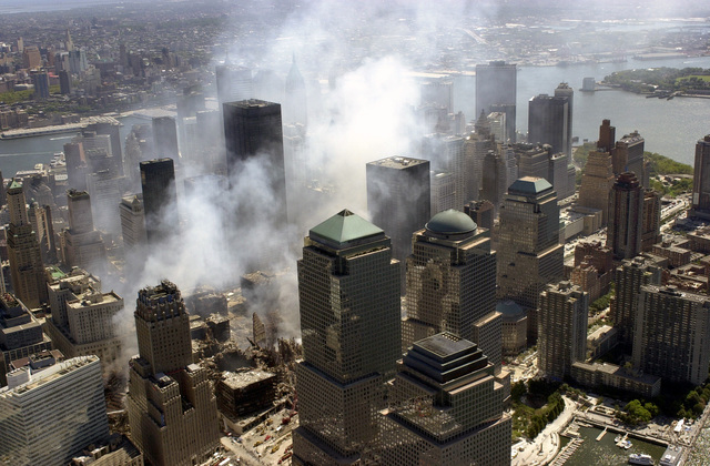 An aerial view, days after the terrorist attacks on American soil, the towers of the World Trade Center (WTC) sit as a pile of rubble in the streets of New York City.   The rescue and recovery efforts continue with tons of debris slowly removed from the site. The view is to the south, the World Financial Center (WFC) towers π American Express (pyramid), WFC tower two (dome) and WFC tower 1 (Oppenheimer, Dow Jones). Governors Island in Upper New York Bay is in the background