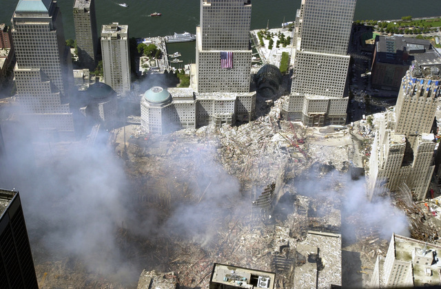 An aerial view, days after the terrorist attacks on American soil, the towers of the World Trade Center sit as a pile of rubble in the streets of New York City. The rescue and recovery efforts continue with tons of debris slowly removed from the site. The view is to the west, with an American flag draped on one of the World Financial Center (WFC) towers. The Hudson River is in the background