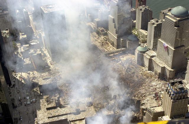 An aerial view, days after the terrorist attacks on American soil, the towers of the World Trade Center (WTC) sit as a pile of rubble in the streets of New York City. The rescue and recovery efforts continue with tons of debris slowly removed from the site. The view is toward the west, with an American flag draped on World Financial Center (WFC) tower two. The Hudson River is in the background