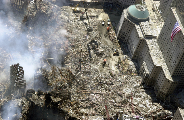 An aerial view, days after the terrorist attacks on American soil, the towers of the World Trade Center (WTC) sit as a pile of rubble in the streets of New York City. The rescue and recovery efforts continue with tons of debris slowly removed from the site. The view is toward the south, with an American flag draped on one of the World Financial Center (WFC) towers