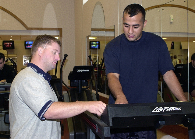 Michael Denny, (left), 100th Services Squadron, Base Fitness Center, RAF Mildenhall, United Kingdom gives Army SPECIALIST Mohamed Hedayet, temporarily attached to the 352nd Operations Support Squadron a quick lesson on how the treadmill works