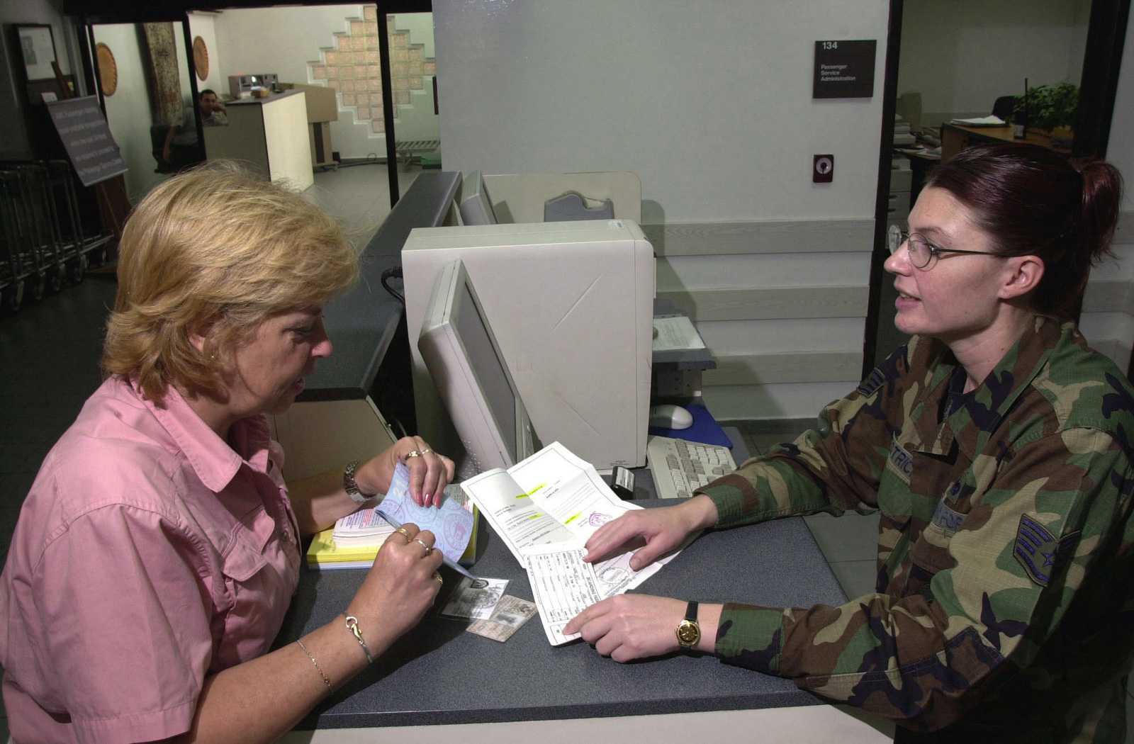 Mrs. Theresa Sorenson (left) gets assistance from US Air Force (USAF) STAFF Sergeant (SSGT) Veronica Westrich, 728th Air Mobility Squadron (AMS) Passenger Service Supervisor, as she makes arrangements for airline tickets, inside the terminal at Incirlik Air Base (AB), Turkey