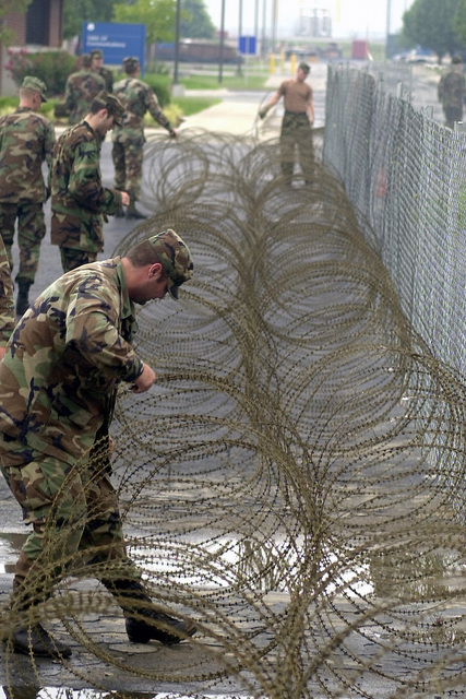 Soldiers from the 1ST Battalion, 279th Infantry, Oklahoma National Guard, called in from a local field training exercise, string razor wire along the fence of a civilian-contractor construction site on the Oklahoma Air National Guard Base, Tulsa International Airport. The extra measure was initiated in response to the terrorist attacks on World Trade Center and the Pentagon on September 11, 2001